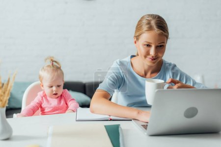 Selective focus of woman with cup working on laptop near baby girl at table