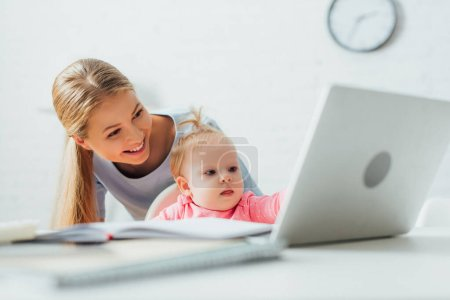Selective focus of mother standing near kid looking at laptop and stationery on table