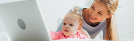Photo for Panoramic crop of infant girl looking at laptop near mother at home - Royalty Free Image