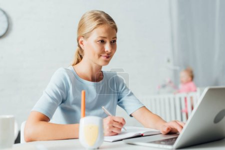 Selective focus of woman working with laptop and notebook near baby monitor on table