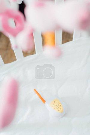 Photo pour Concentration sélective du moniteur de bébé dans le berceau avec des jouets mous - image libre de droit