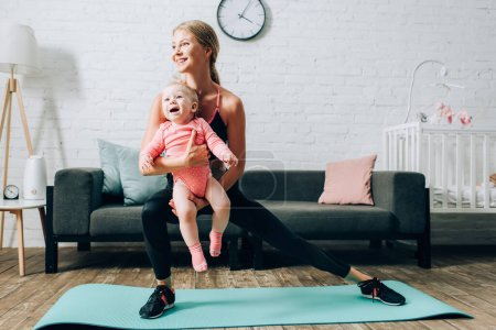 Woman training on fitness mat and holding baby daughter at home