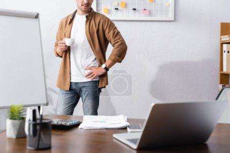 Photo pour Vue recadrée de l'homme d'affaires en vêtements décontractés tenant tasse de café tout en se tenant avec la main sur la hanche au bureau - image libre de droit