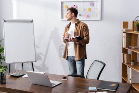 Photo pour Homme d'affaires en vêtements décontractés regardant loin tout en tenant un cahier et tasse de café dans le bureau - image libre de droit