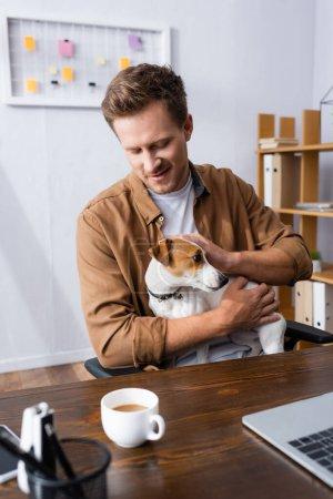 Photo pour Homme d'affaires en vêtements décontractés câlins Jack Russell Terrier chien assis sur le lieu de travail près de tasse de café - image libre de droit