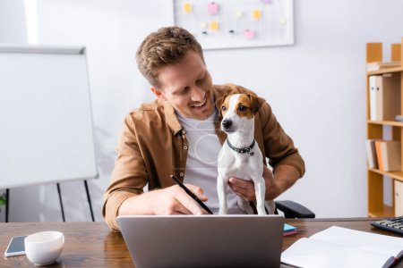 young businessman pointing with finger at laptop while working with jack russell terrier dog in office