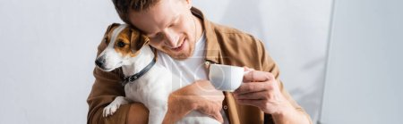horizontal image of businessman cuddling jack russell terrier dog while holding cup of coffee in office