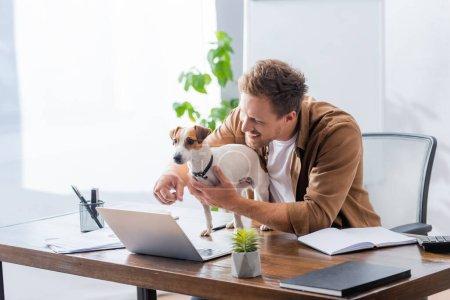 Photo pour Homme d'affaires pointant avec le doigt à l'ordinateur portable près de Jack Russell Terrier chien - image libre de droit