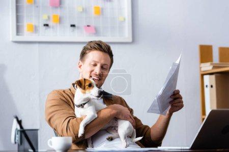 Photo pour Homme d'affaires tenant des papiers tout en câlinant Jack Russell terrier chien dans le bureau - image libre de droit