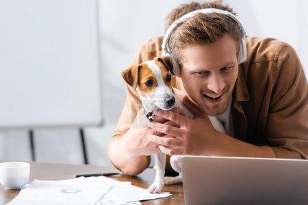 Photo pour Jeune homme d'affaires dans les écouteurs sans fil câlins jack russell terrier chien sur le lieu de travail près d'un ordinateur portable - image libre de droit