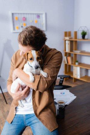 Photo pour Homme d'affaires en vêtements décontractés câlins Jack Russell Terrier chien assis sur le bureau - image libre de droit