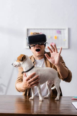 Photo for Scared businessman in vr headset gesturing near jack russell terrier dog in office - Royalty Free Image
