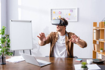 Photo for Excited businessman gesturing while using vr headset at workplace - Royalty Free Image