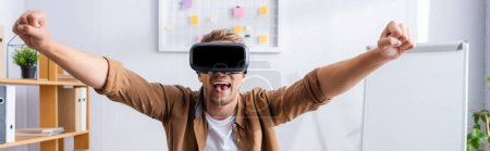 Photo pour Panoramic shot of excited businessman in vr headset showing winner gesture in office - image libre de droit