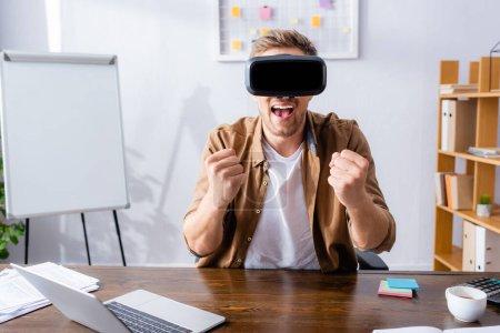 Photo pour Excité homme d'affaires montrant geste gagnant tout en utilisant vr casque sur le lieu de travail - image libre de droit