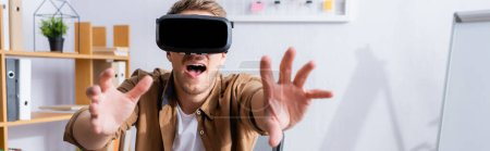 Photo for Horizontal image of excited businessman gesturing while using vr headset in office - Royalty Free Image