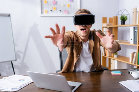 excited businessman in vr headset gesturing near laptop at workplace
