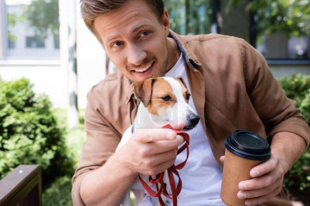 young man with jack russell terrier dog holding paper cup and pointing with finger