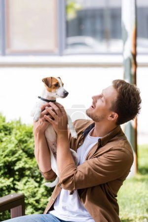 young man in casual clothes holding jack russell terrier dog while sitting on bench outside
