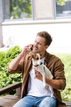 Photo pour Jeune homme en vêtements décontractés tenant jack russell terrier chien et parler sur smartphone tout en étant assis sur le banc - image libre de droit