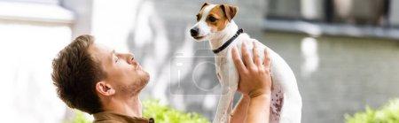 Photo pour Prise de vue panoramique de l'homme élevant Jack Russell terrier chien sur les mains tout en se tenant sur la rue - image libre de droit