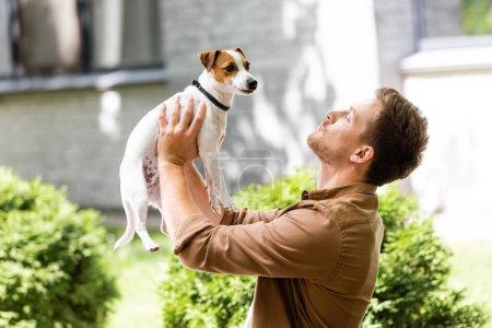 Photo pour Jeune homme debout à l'extérieur et élevant Jack Russell terrier chien sur les mains - image libre de droit