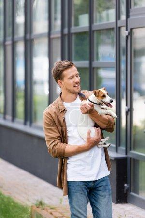 Photo pour Jeune homme en vêtements décontractés debout près du bâtiment avec façade en verre et tenant Jack Russell Terrier chien - image libre de droit