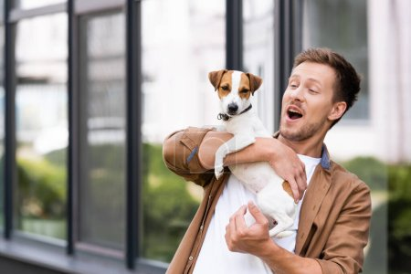 Photo for Excited man with open mouth holding jack russell terrier dog on city street - Royalty Free Image