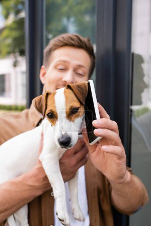 Photo pour Selective focus of young man holding mobile phone near ear of jack russell terrier dog on street - image libre de droit