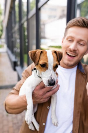 selective focus of young man holding jack russell terrier dog on street