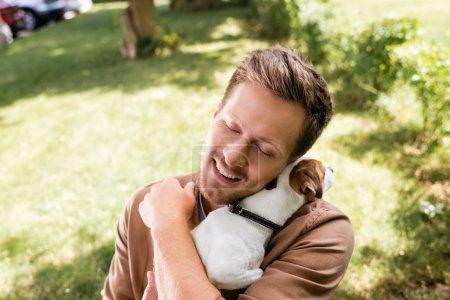 Photo pour Jeune homme avec les yeux fermés tenant et câlinant Jack Russell Terrier chien dans le parc - image libre de droit