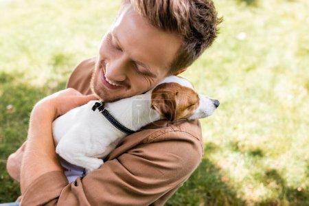 Photo pour Vue grand angle du jeune homme les yeux fermés tenant le chien terrier Jack Russell blanc avec des taches brunes sur la tête - image libre de droit