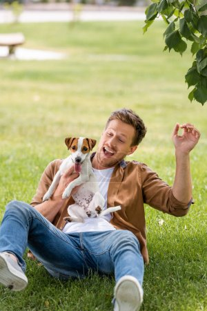 Photo pour Excité homme en vêtements décontractés tenant Jack Russell terrier chien tout en s'amusant sur la pelouse - image libre de droit