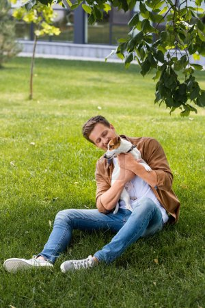 young man in brown shirt and jeans sitting on grass and cuddling jack russell terrier dog
