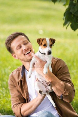 Photo pour Jeune homme en chemise marron tenant Jack blanc russell terrier chien avec des taches sur la tête - image libre de droit