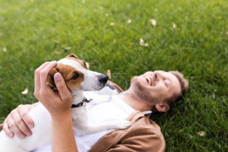 Photo pour Foyer sélectif de l'homme couché avec Jack Russell terrier chien sur herbe verte avec les yeux fermés - image libre de droit