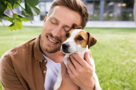young man with closed eyes holding white jack russell terrier dog with brown spots on head