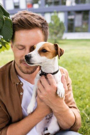 Photo pour Jeune homme les yeux fermés tenant Jack Russell terrier chien avec des taches brunes sur la tête - image libre de droit