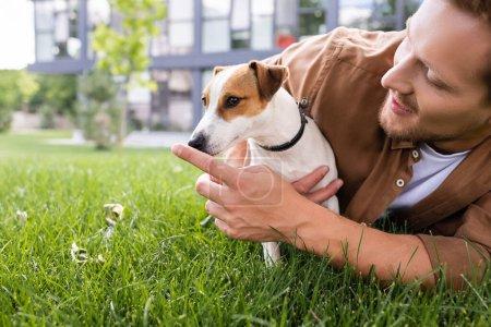 Photo pour Jeune homme couché sur la pelouse verte et toucher le nez du chien Jack Russell Terrier - image libre de droit