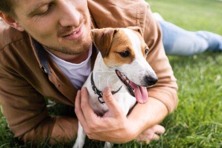 Photo pour Vue partielle du jeune homme câlin Jack Russell Terrier chien tout en se relaxant sur l'herbe verte - image libre de droit