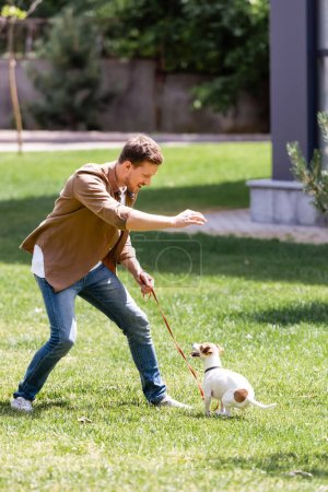 Enfoque selectivo del hombre en jeans jugando con jack russell terrier con correa en el parque