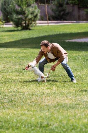 Photo pour Focus sélectif de l'homme excité tenant la laisse tout en jouant avec Jack Russell terrier dans le parc - image libre de droit