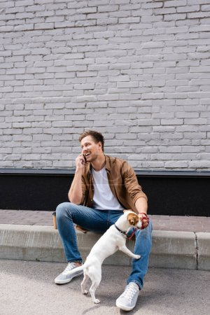 Photo for Young man talking on smartphone near jack russell terrier on leash on urban street - Royalty Free Image