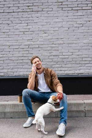 Man holding jack russell terrier on leash while talking on smartphone near coffee to go on urban street
