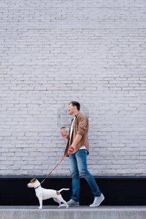Niedrige Blickwinkel von Mann mit Coffee to go Jack Russell Terrier an der Leine in der Nähe von Gebäude