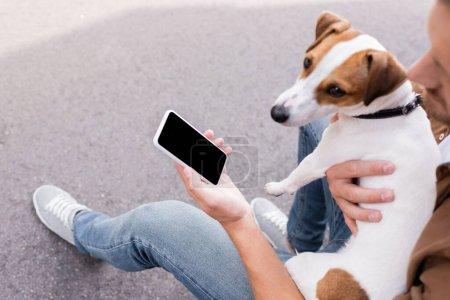 Photo pour Focus sélectif de l'homme tenant smartphone avec écran vierge et câlin jack russell terrier à l'extérieur - image libre de droit