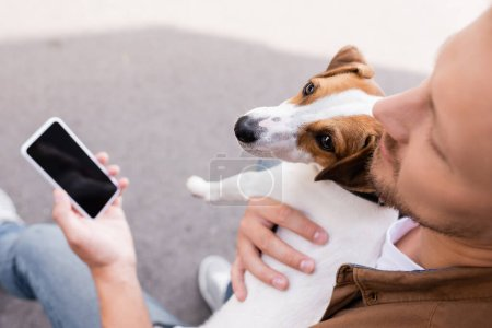Photo pour Selective focus of man embracing jack russell terrier and holding smartphone with blank screen outdoors - image libre de droit