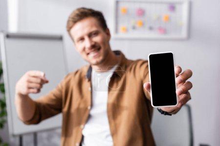 Photo pour Concentration sélective de l'homme d'affaires pointant du doigt le smartphone avec écran vierge dans le bureau - image libre de droit