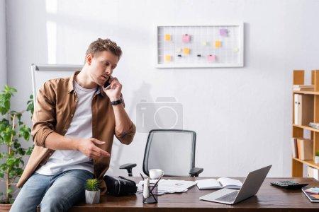 Junge Geschäftsmann spricht auf Smartphone in der Nähe von Laptop und vr Headset auf dem Tisch im Büro