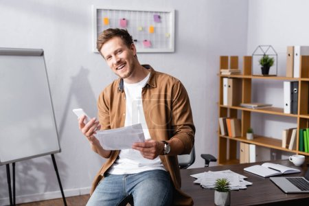 Photo for Young businessman with smartphone and papers looking at camera in office - Royalty Free Image